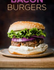 A bacon burger on a hamburger bun, with layers of lettuce and purple onion.
