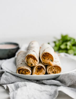 A plate with baked chicken taquitos on it.