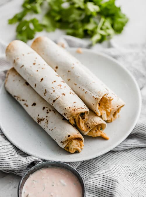 Baked Chicken Taquitos with cilantro in the background.