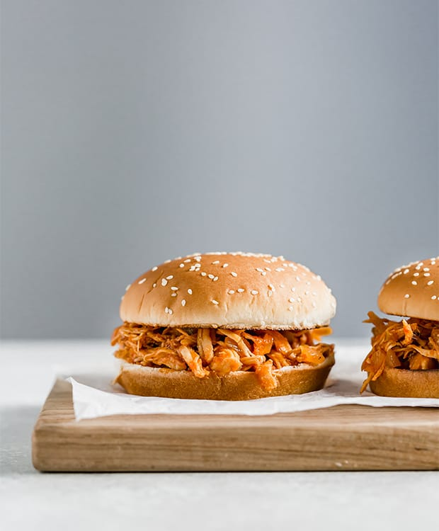 A BBQ chicken sandwich set on a wooden cutting board.