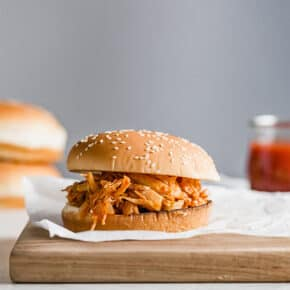 A BBQ chicken sandwich on a wooden board, with hamburger buns stacked in the background.