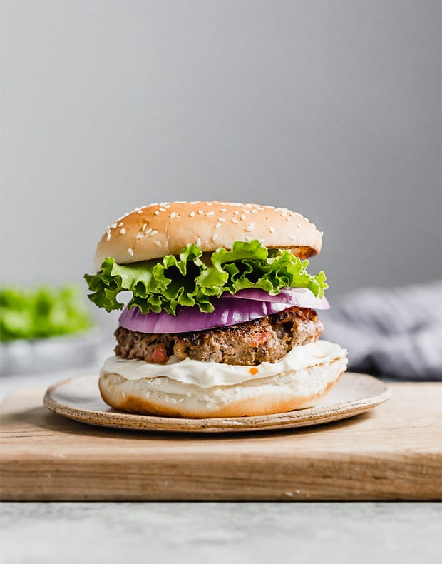 The best bacon burger on a hamburger bun, topped with lettuce and red onion.
