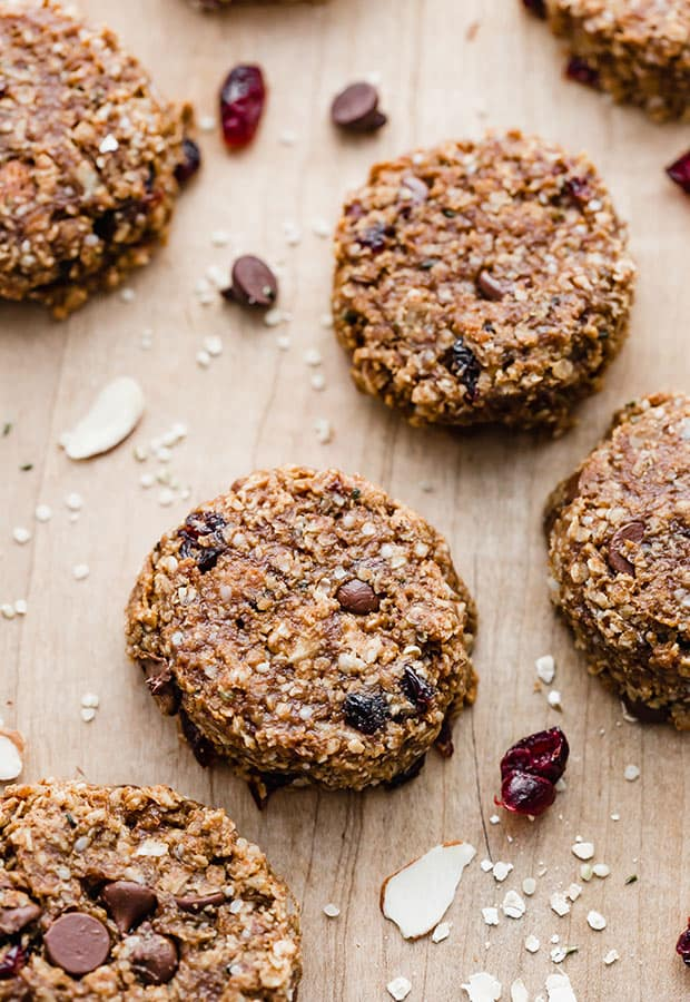 Breakfast cookies sitting on a wooden cutting board with dried cranberries next to the cookies.