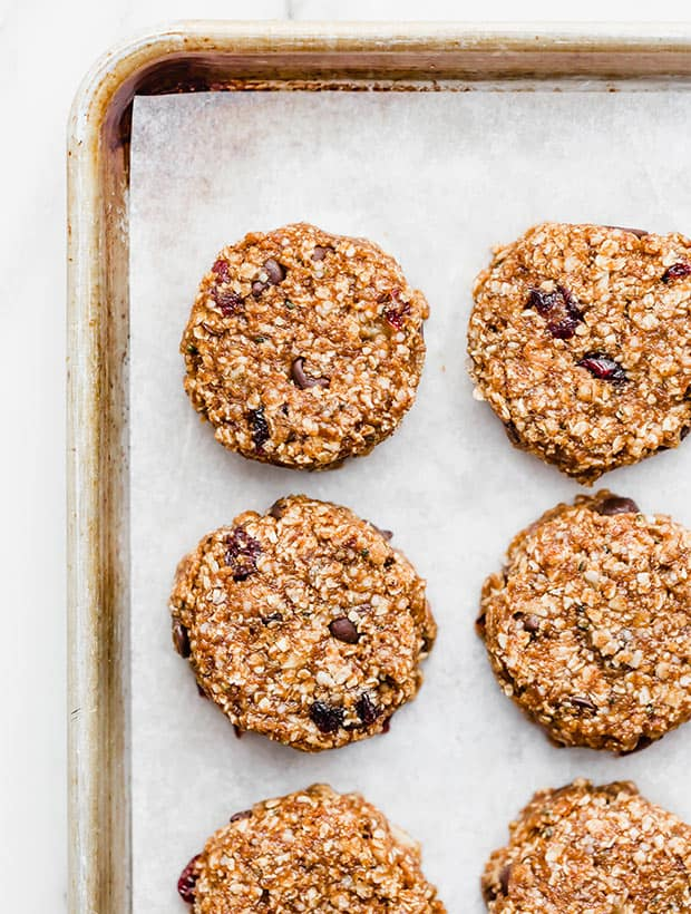 A baking sheet lined with parchment paper, and breakfast cookies neatly placed on the sheet.