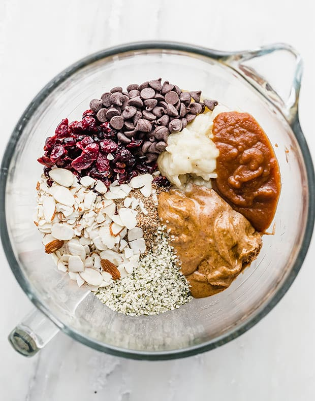A glass mixing bowl with all of the healthy ingredients for making breakfast cookies.