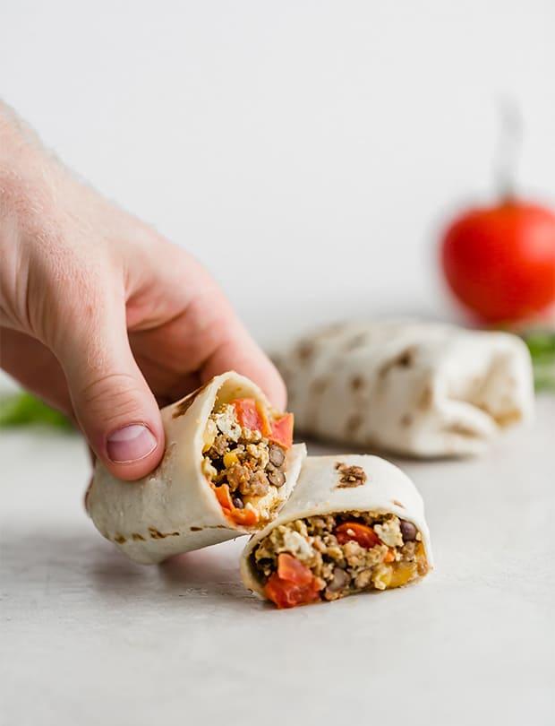 A hand grabbing a Southwestern Sausage and Egg Burritos