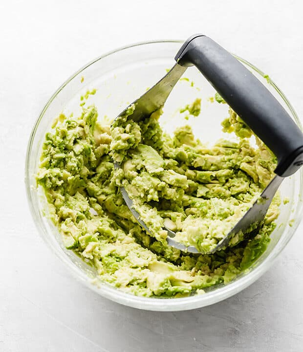 A glass bowl with a pastry cutter mashing avocados.