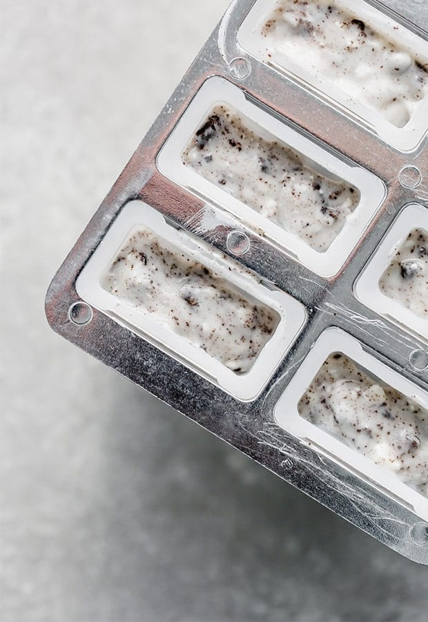 A popsicle mold full of cookies and cream mixture.