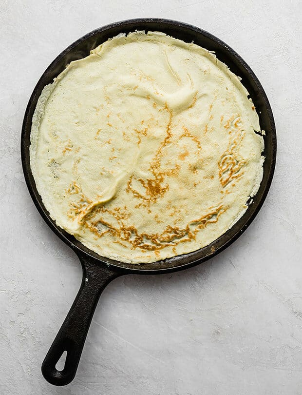A cast iron skillet cooking an English pancake.