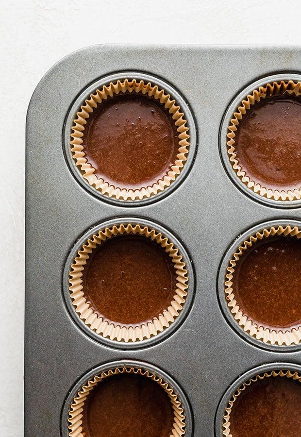 Cupcake tin filled with chocolate cupcake batter.