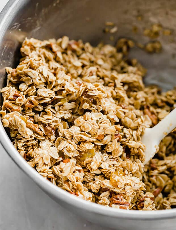 Homemade granola bar ingredients being mixed in a metal bowl.