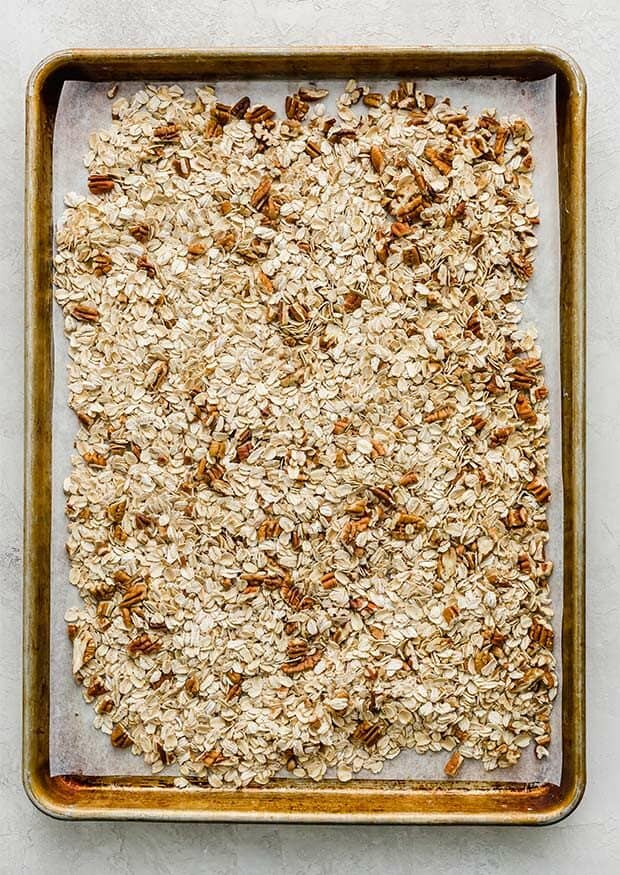 A baking sheet with rolled oats and chopped pecans on it.