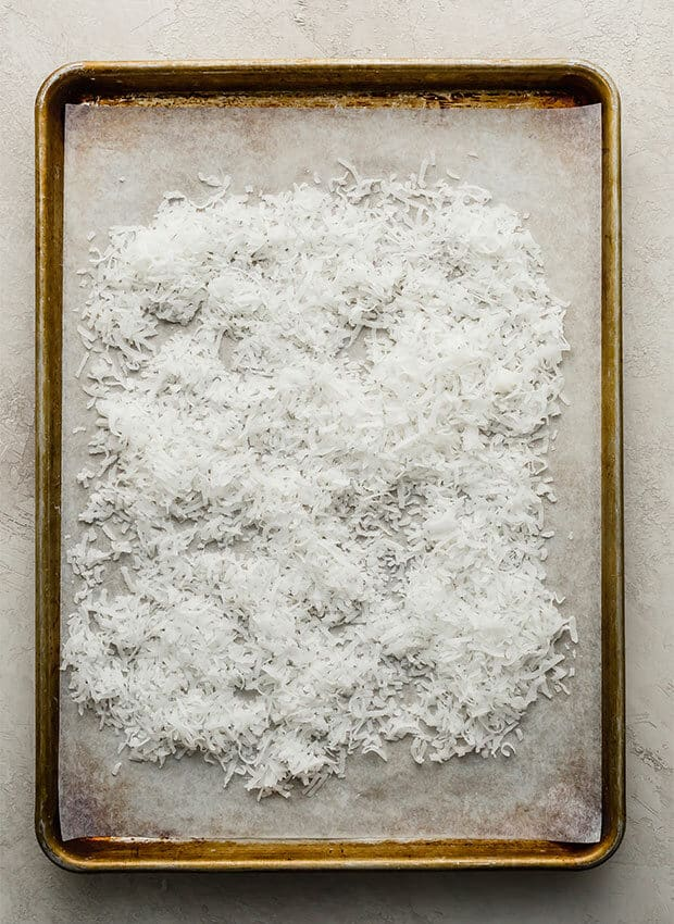 A baking sheet with shredded coconut on it, prior to baking and toasting the coconut.