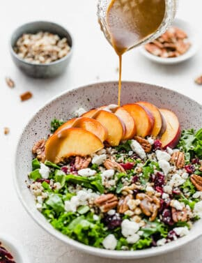 A balsamic dressing being drizzled over fresh peaches on a bed of kale and quinoa salad.