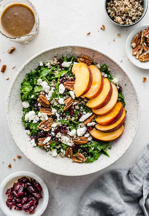 Kale and quinoa salad with fresh peaches, pecans, and feta cheese.