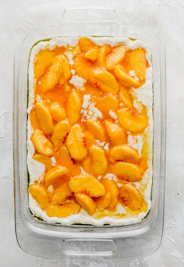A casserole dish with unbaked peach cobbler.