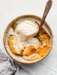 An old fashioned easy peach cobbler recipe, with a scoop of ice cream overtop and a spoon.