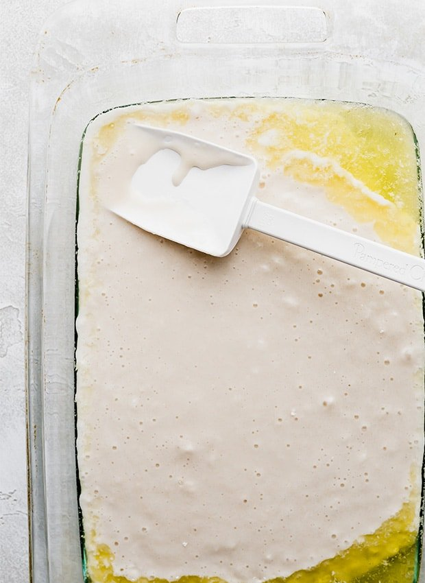 A glass 13x9 inch pan with melted butter and peach cobbler batter being spread over the butter.