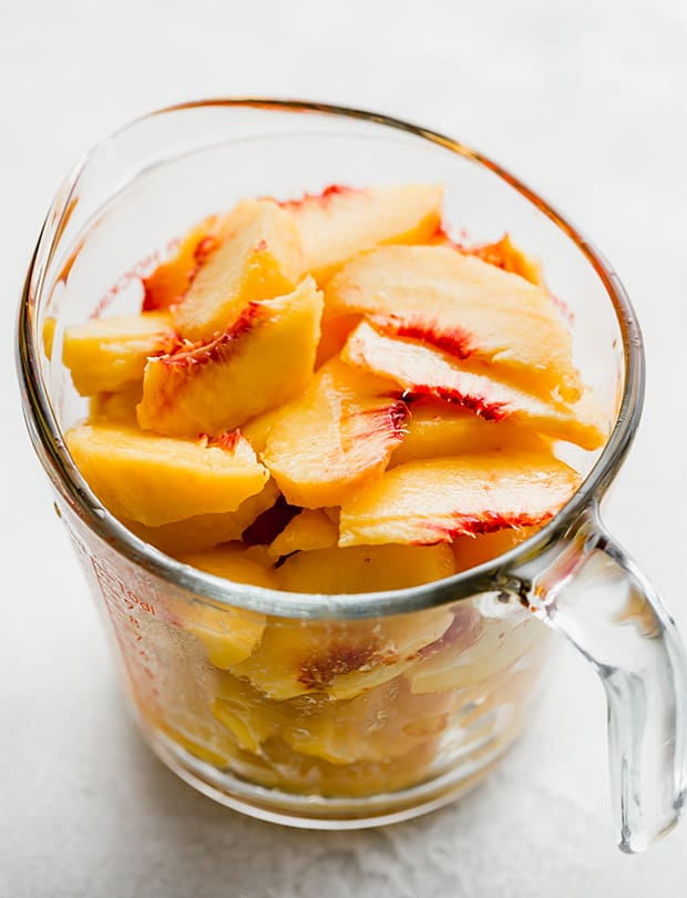 A glass measuring cup full of fresh sliced peaches, for making easy peach cobbler.