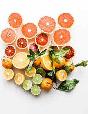 Photo by Brooke Lark, citrus fruits with surrounding greenery.