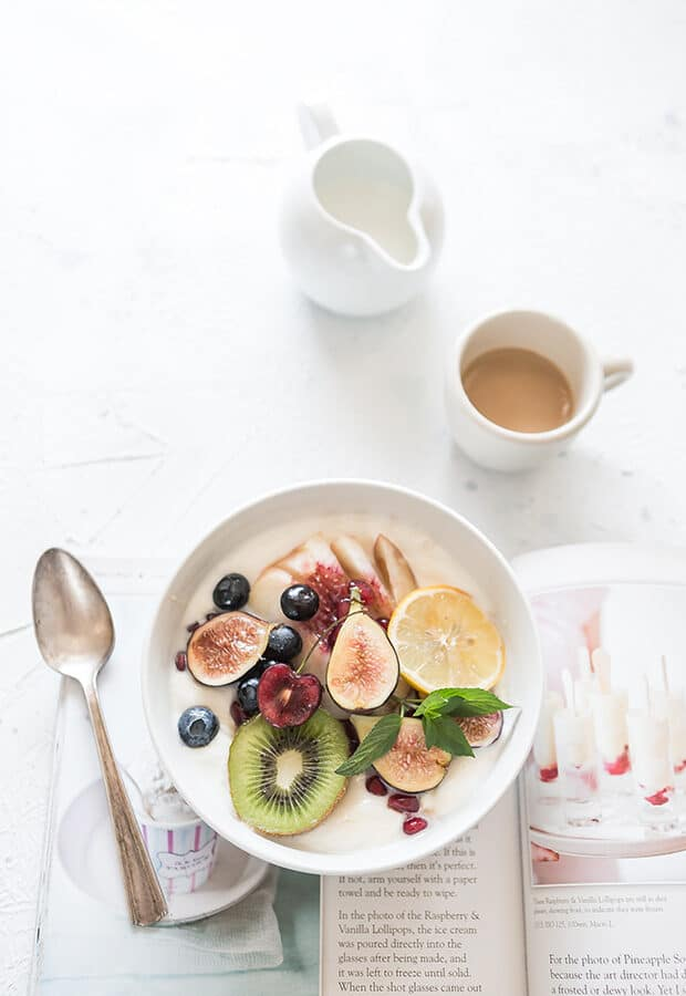 A white bowl with fruits next to a spoon.