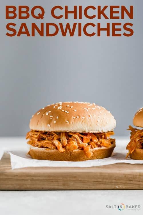 A BBQ chicken sandwich set on a wooden cutting board.