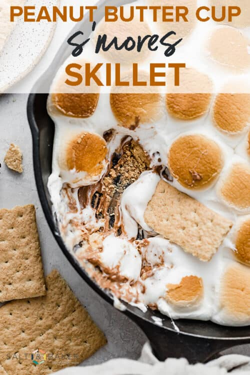 A graham cracker dipping into the melty marshmallows and exposing the melted Reeses peanut butter cup underneath the Reeses Peanut Butter Cup S'mores Skillet.