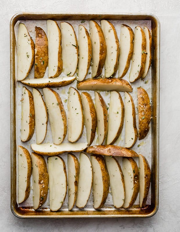 A baking sheet full of potato wedges prior to baking.