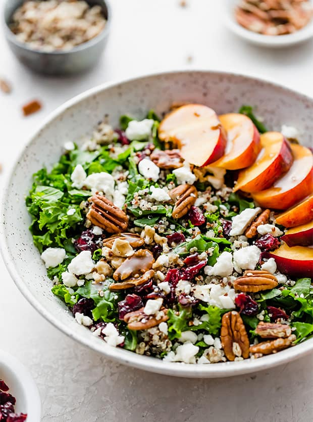 A kale and quinoa salad with pecans, feta cheese, fresh peaches, and craisins.