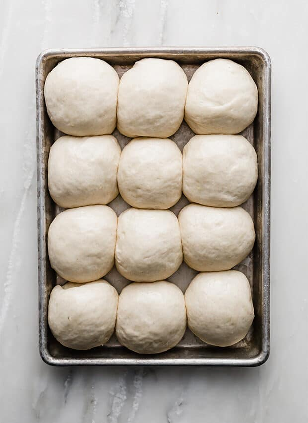 A baking sheet with dinner rolls.