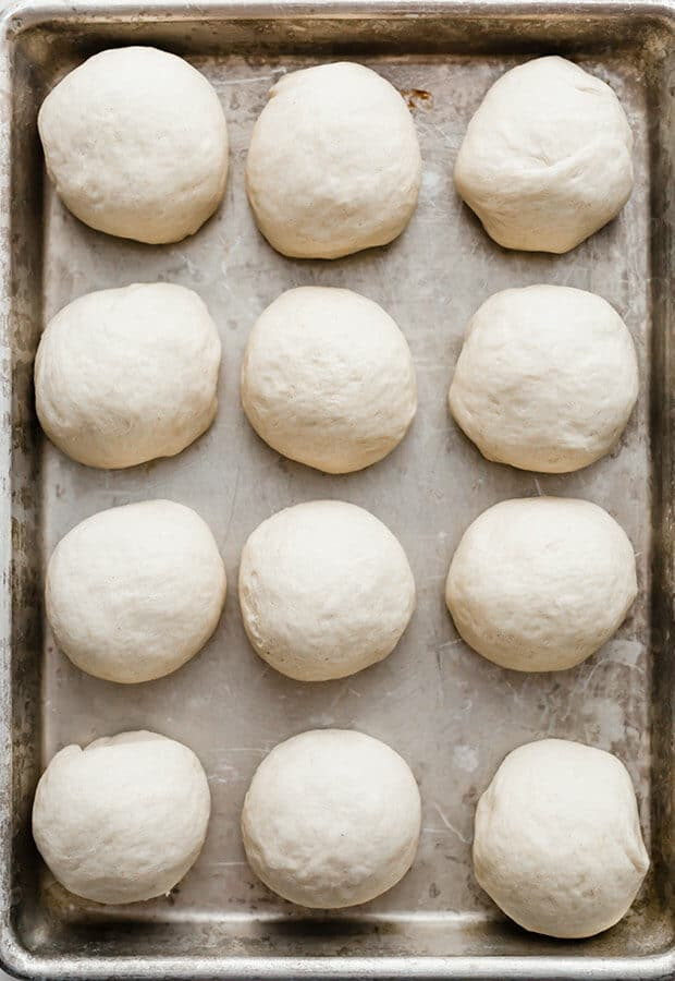 A baking sheet with balls of roll dough.