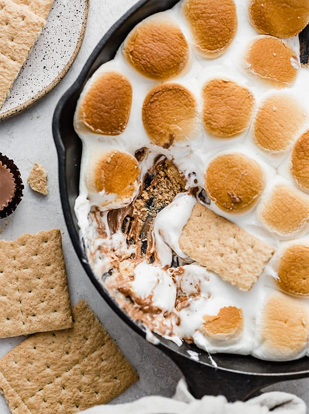 A graham cracker scooping up some Reeses Peanut Butter Cup S'mores Skillet