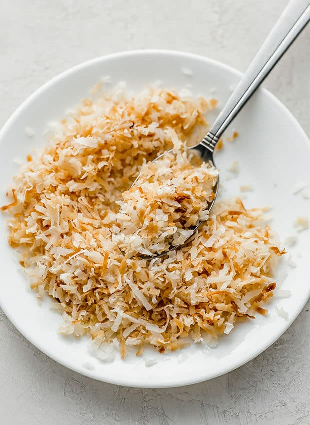A white plate with toasted coconut made in the microwave.