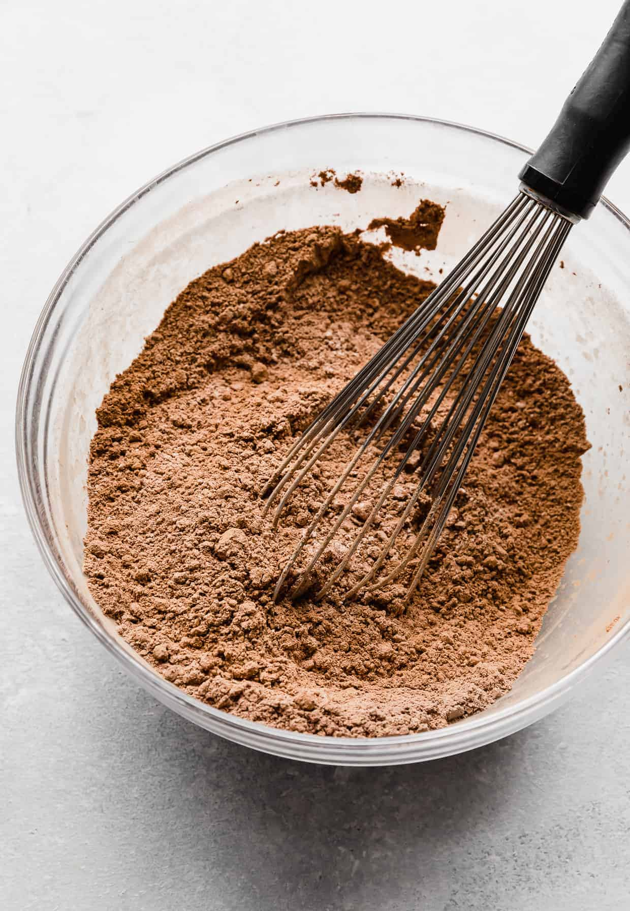 A light brown colored dry ingredients in a glass bowl with a whisk mixing it together.