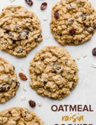 Soft oatmeal raisin cookies surrounded by oats and raisins.
