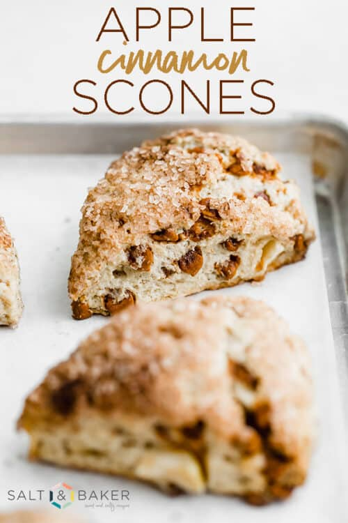 A close up photo of an apple cinnamon scone on a parchment lined baking sheet.