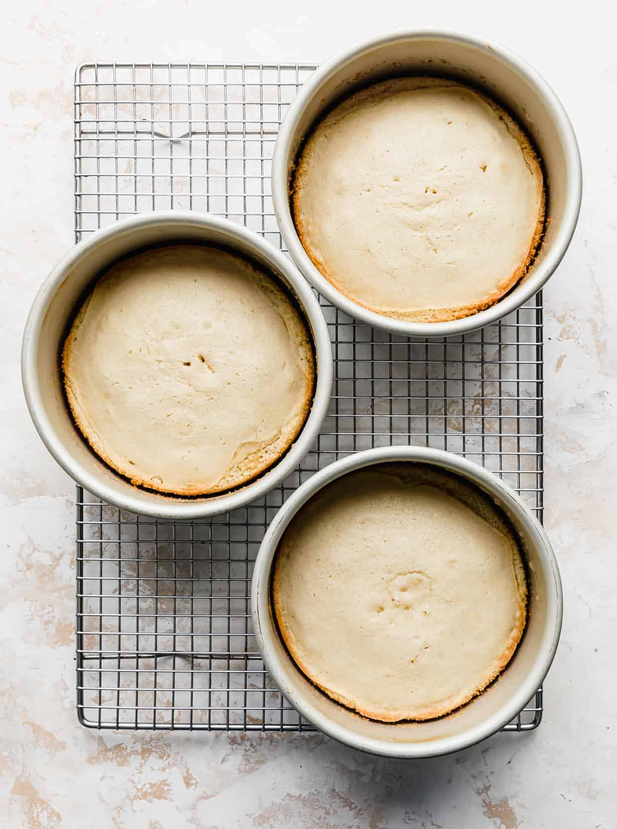 Three baked vanilla cake rounds in cake pans on a wire cooling rack.