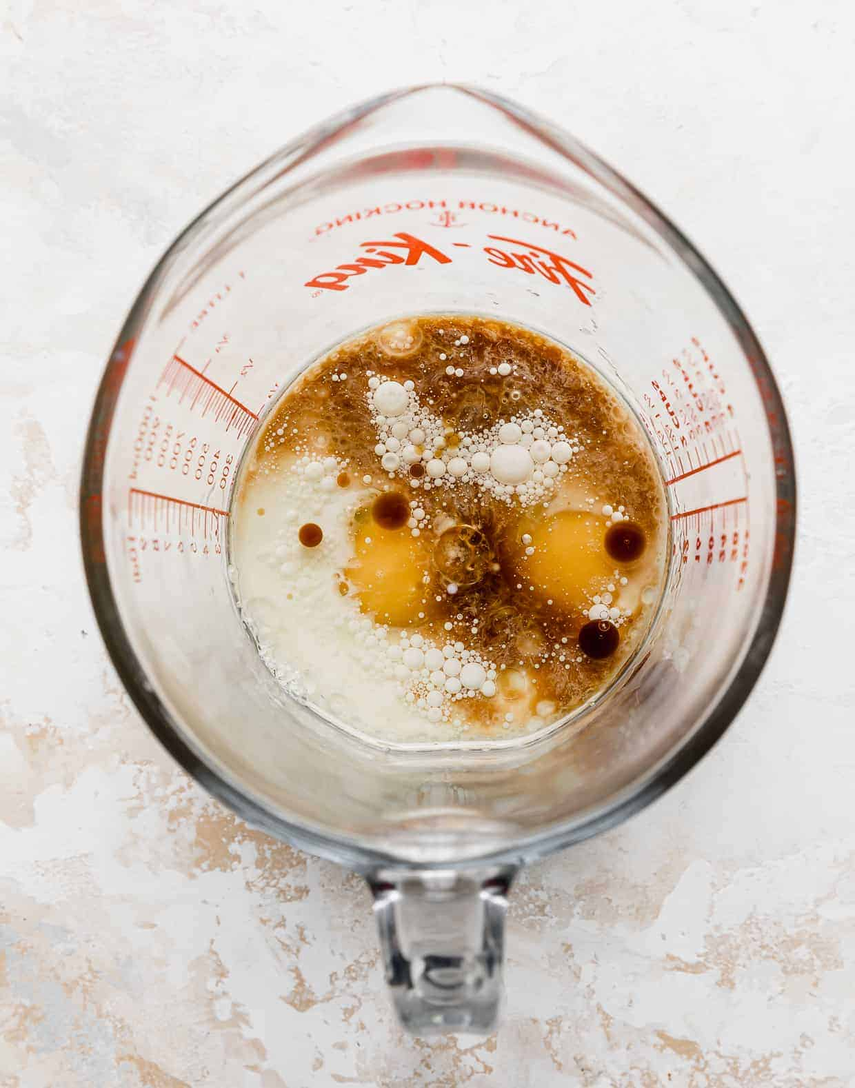 A liquid measuring cup with eggs, vanilla, buttermilk in it.