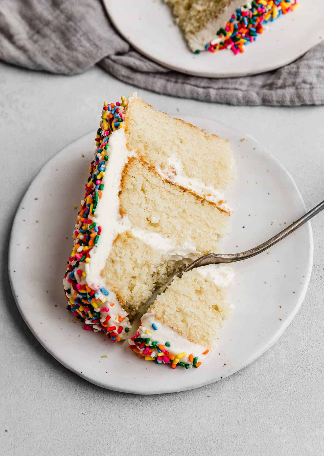 A slice of a multi colored sprinkle smash cake on a white plate