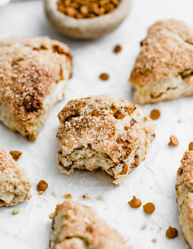 Apple cinnamon scones surrounded by cinnamon chips.