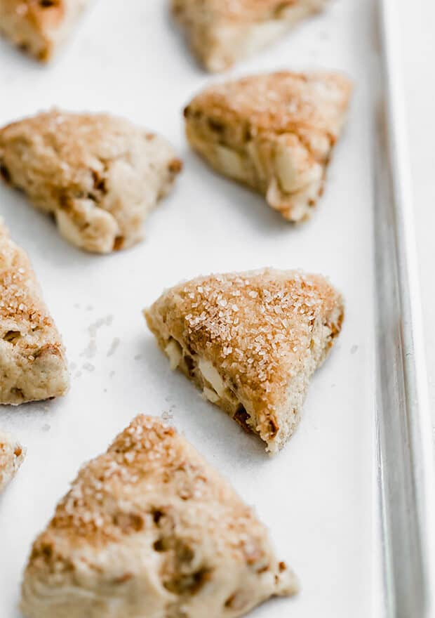 Apple cinnamon scones on a parchment lined baking sheet prior to baking.