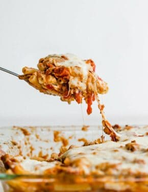 A spoon scooping up pasta from a casserole dish, Easy Baked Ziti.