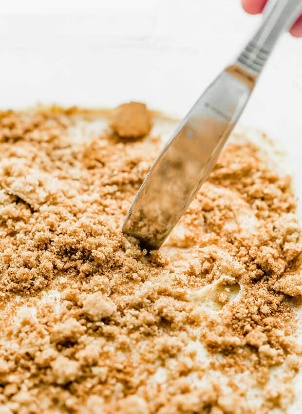 A knife swirling the cinnamon sugar mixture into the cake batter.