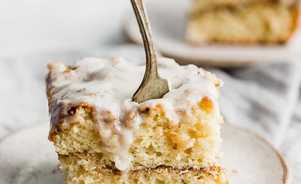 A fork digging into a slice of cinnamon roll cake.