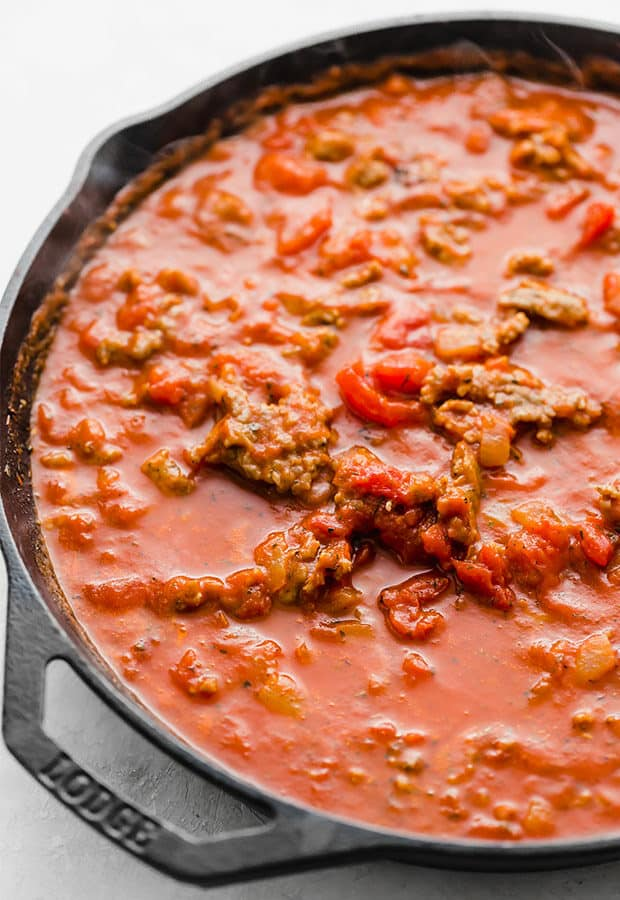 A skillet with the red sauce and sausage for the easy baked ziti recipe.