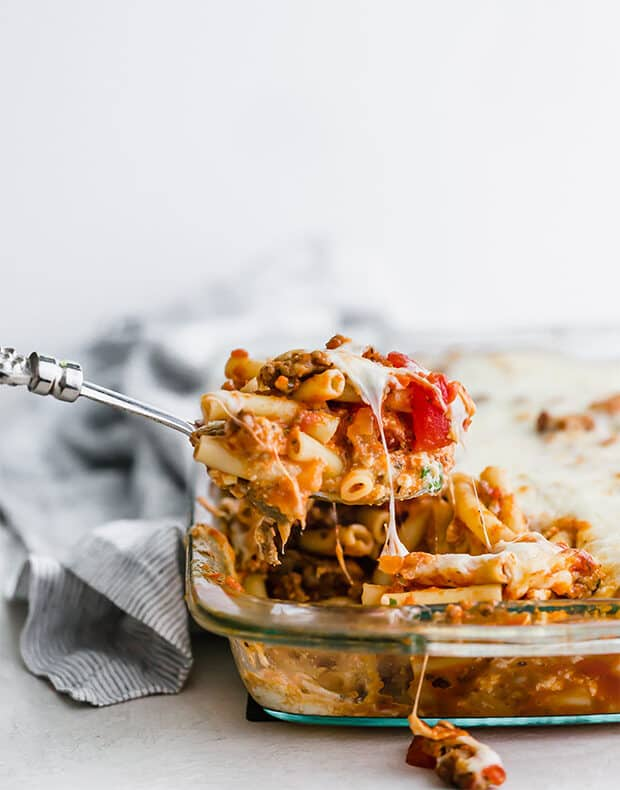 A spoon scooping out a portion of the baked ziti.