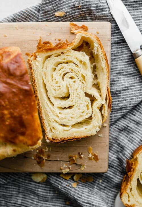 A slice of Flaky Brioche laying on a wooden cutting board.