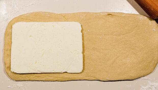 Brioche dough rolled out, with a large square of flattened butter on one side of the rectangle.