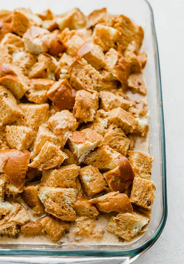 A casserole dish with cubed challah bread soaking in a pumpkin spice egg mixture.
