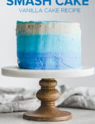 A three tiered blue ombre smash cake on a cake stand.